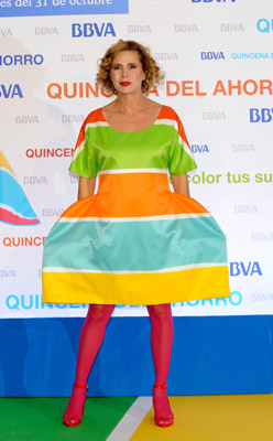 First of all, this is a fashion designer, yes, a fashion designer, Agatha Ruiz de la Prada. No way a relation to Muccia...or if so...from Muccia's mother's side, twice removed...by marriage. It looks like she's wearing a twister board that got run over by a steamroller.